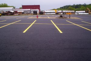 A newly paved commercial parking lot with yellow panted lines